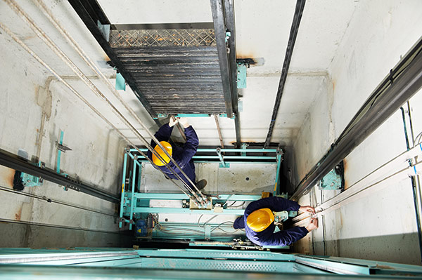 Elevator mechanics repairing an elevator inside the elevator shaft