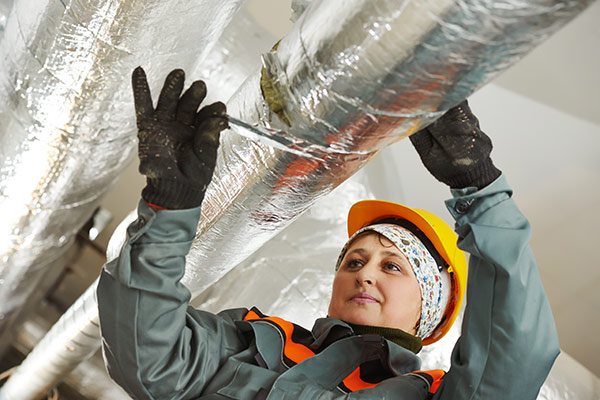 A female mechanical insulator at work